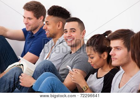 Happy College Student Sitting With Classmates