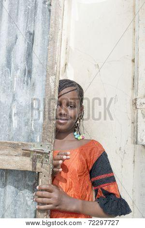 Unidentified girl partially hiding behind a door