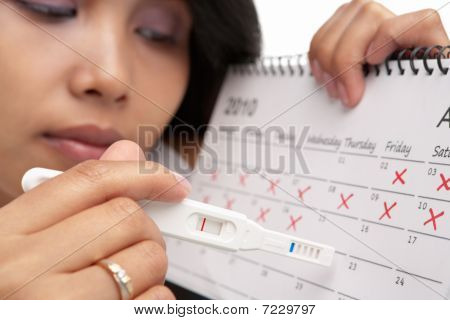 Sad Woman With Negative Pregnancy Test And Calendar