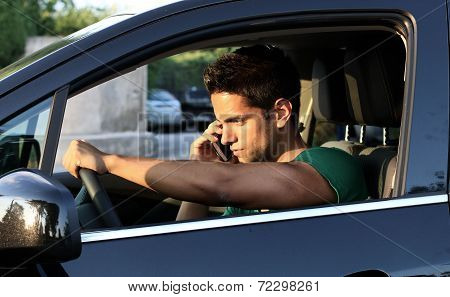 young man driving and speaking on mobile phone