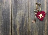 image of skeleton key  - Red heart and bronze skeleton key hanging on rustic wooden fence - JPG
