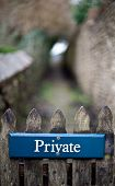 stock photo of old stone fence  - Blue sign on an old wooden gate in a fence says private - JPG
