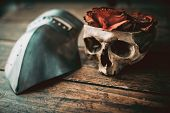 stock photo of mystique  - Skull with roses and armor mask on a wood table - JPG