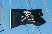 stock photo of skull crossbones flag  - Black skull and crossbones pirate flag against a blue sky - JPG
