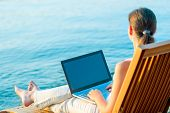 picture of barefoot  - barefoot girl with a laptop on the beach working - JPG