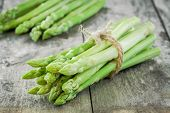 foto of bundle  - bundle of of ripe organic asparagus on a wooden background - JPG