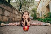 stock photo of do splits  - small pretty girl doing splits and looking for red apple - JPG
