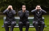 pic of bench  - businessman sitting on a bench three times covering his earseyes and mouth - JPG