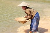 stock photo of ou  - washing gold in the river woman sieves rock at river Nam Ou in Laos - JPG