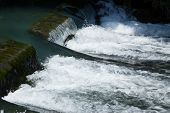 foto of dam  - Water flowing over a small rock dam - JPG