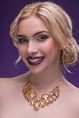 stock photo of half naked  - Half-length portrait of beautiful sexy smiling blonde with violet tempting lips and perfect skin wearing precious necklace on her naked shoulders looking at us seductively isolated on dark background ** Note: Shallow depth of field - JPG