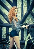 image of woman red blouse  - Beautiful girl wearing ultramarine blouse and black sexy shorts in park with bicycle - JPG
