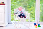 pic of daycare  - Cute funny baby adorable little boy wearing a colorful shirt relaxing in a white rocking chair next to a big garden view window at home or daycare center - JPG
