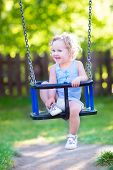 picture of playground  - Happy laughing toddler girl with curly hair wearing a blue dress enjoying a swing ride on a sunny summer playground in a park - JPG