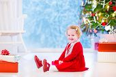 picture of girl next door  - Cute curly little girl in a red dress and white pearl necklace playing under a Christmas tree with presents sitting on the floor of a white living room with rocking chair next to a window into a snowy winter garden - JPG