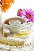 pic of tea party  - A bright sunny ladies tea party with fresh flowers cup of tea with fresh lemon slices on fine china with lemon biscotti cookies vertical with copy space perfect for Mother - JPG