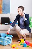 image of toy phone  - Young mother talking on phone and cleaning up toys - JPG