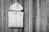 image of hooded sweatshirt  - White hooded sweater on dark wood background - JPG
