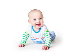 picture of teething baby  - Happy Laughing Baby Boy In A Colorful Shirt Playing On His Tummy - JPG