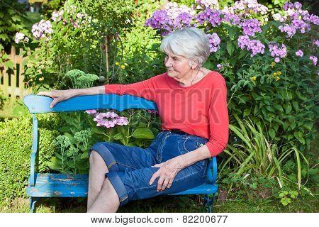 Senior Woman Relaxing At The Garden Bench