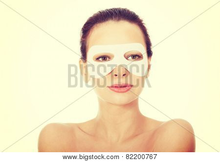 Young beautiful spa woman with collagen eye mask.