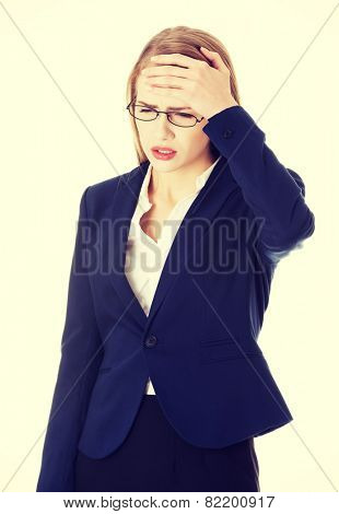 Beautiful business woman is touching her forehead, checking fever.