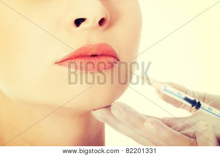 Young beautiful woman doing injection into mouth. Plastic surgery concept.