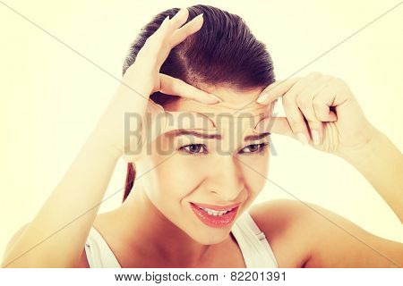 Young woman checking her wrinkles on forehead.