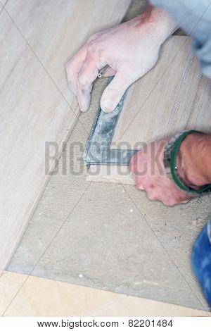Tiler installs ceramic tiles at home.