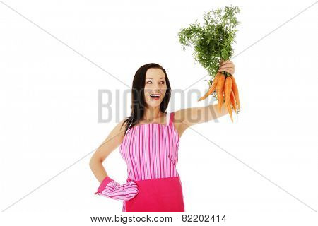 Attractive woman in kitchen apron holds bunch of carrots.