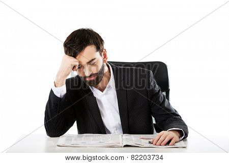 Tired businessman reading newspaper in the office.