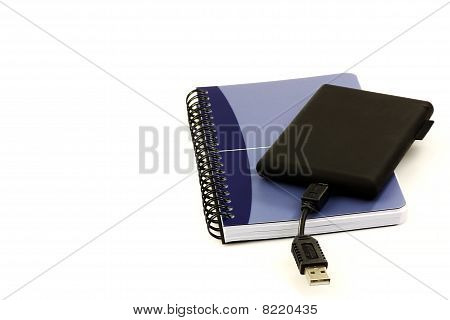 Old fashioned notebook and an external hard drive,