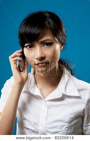 Worried, closeup portrait of Asian business woman on studio blue background.
