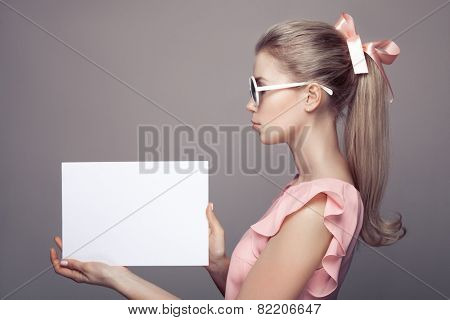 Fashion Woman With Sunglasses Holding Empty Paper Blank In Hands.