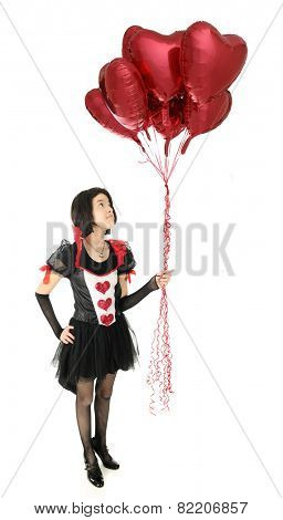 A pretty young teen in a Valentine dress looking up at the fistful of heart-shaped balloons she  holds.  On a white background.