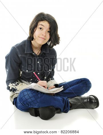 A pretty young teen happily looking at the viewer while sitting cross legged on the floor with pencil and note pad.  On a white background.