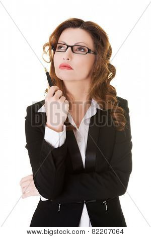 Thinking business woman with pen under chin looking up.