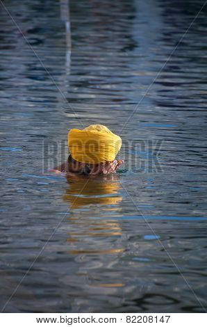 Sikh Man Praying In The Holy Lake At Golden Temple . Amritsar. India