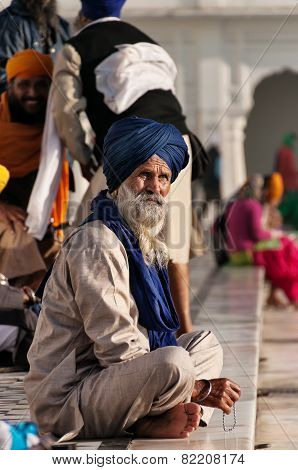 Sikh Man Sitting Near The Lake At Golden Temple In The Early Morning. Amritsar. India