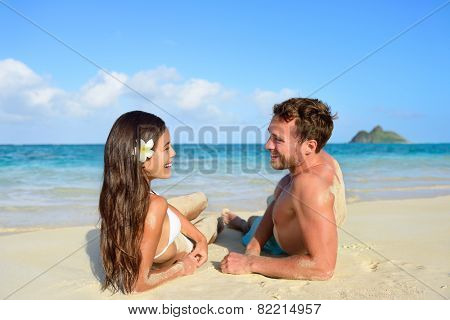 Couple in love relaxing on beach during vacation travel. Happy couple portrait talking together in a happy relationship sun tanning lying on the sand having fun in Hawaii, United States of America.