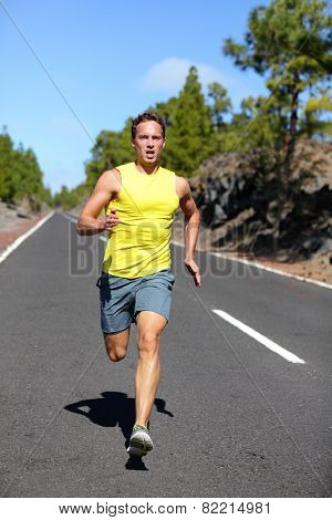 Runner man running sprinting for success on run. Male athlete runner training at fast speed. Muscular fit sport model sprinter exercising sprint on forest road. Full body length of Caucasian model.