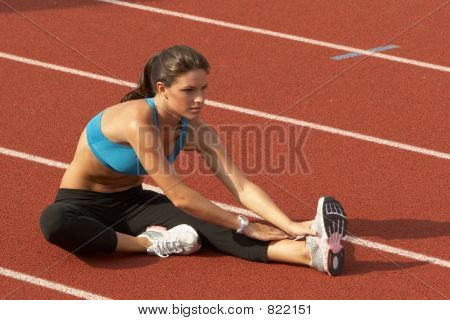 Young Woman in Sports Bra Stretching Leg on Track