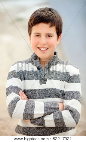 Smiling teenage boy of thirteen with striped sweater folding his arms