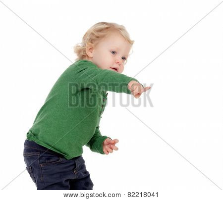 Adorable blond baby indicating something isolated on a white background