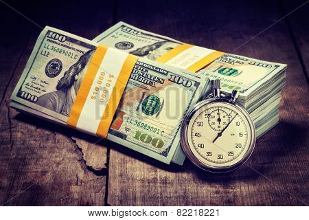 Time is money loan concept background - Vintage retro effect filtered hipster style image of stopwatch and stack of new 100 US dollars 2013 edition banknotes (bills) bundles on wooden background