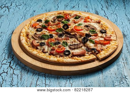 Ham pizza with capsicum, mushrooms, olives and basil leaves on wooden board on blue table