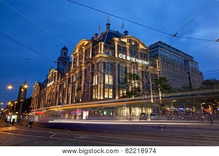 City Tram Passing By De Bijenkorf Store In Dam Square Of Amsterdam