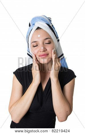 beautiful young woman applying cleaning cream moisturizer to her face