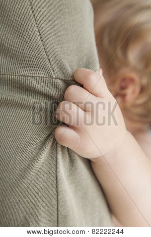 Closeup Baby Hand Holding Mom Dress