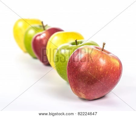 several multicolored apples arranged in line